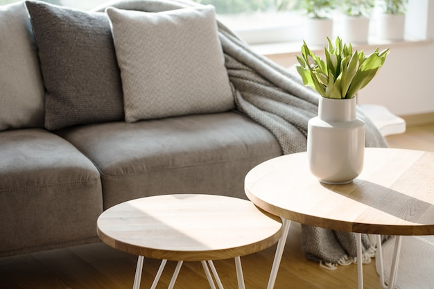 Close-up van tulpen op houten ronde tafel in natuurlijk grijs woonkamerinterieur met een bank
