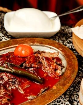 Close up van turkse iskender kebab gegarneerd met tomatensaus en gegrilde peper