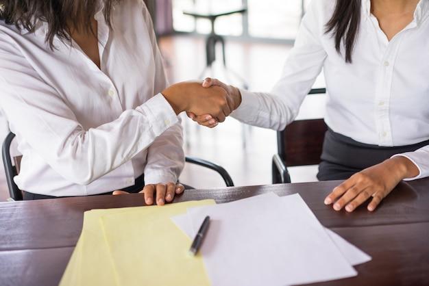 Close-up van twee bedrijfsvrouwen die handen schudden en bij bureau zitten.