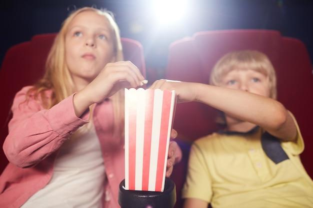 Close-up van twee blonde kinderen die popcornbeker delen tijdens het kijken naar tekenfilms in bioscooptheater, focus op voorgrond, kopieer ruimte