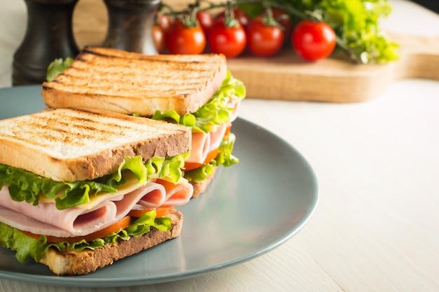 Close-up van twee broodjes met spek, salami, prosciutto en verse groenten op rustieke houten snijplank. club sandwich concept.