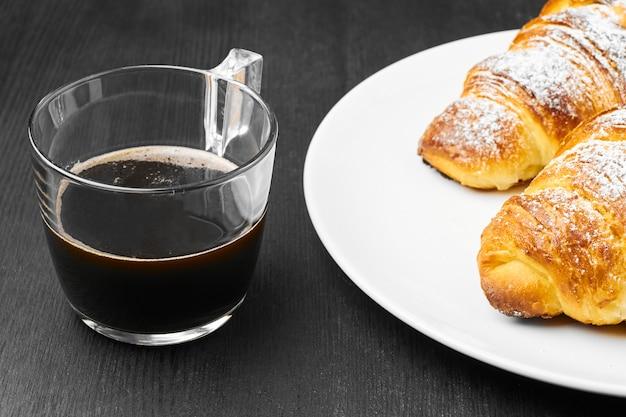 Close-up van twee croissants op een witte plaat en een kopje koffie op een zwarte muur. concept van italiaans ontbijt.
