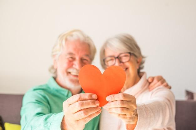 Close-up van twee gelukkige en verliefde senioren die glimlachen en kijken naar de camera die een rood hart bij elkaar houdt - volwassen verliefde mensen