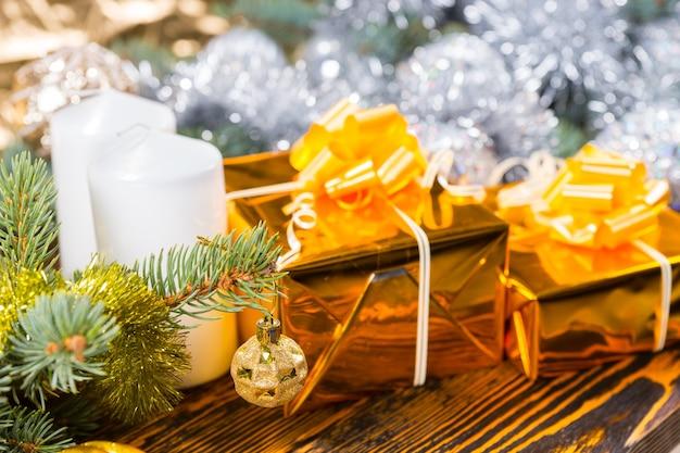Close up van twee geschenken verpakt in goud met bogen naast witte pijler kaarsen op rustieke houten tafel omgeven door groenblijvende takken versierd met klatergoud garland en ballen