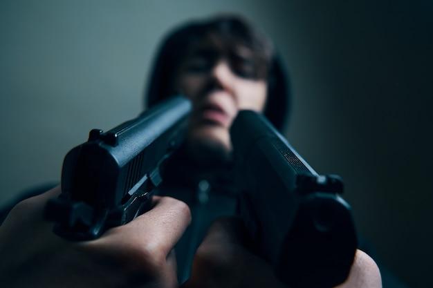 Close-up van twee geweren gericht op het gehavende gezicht van de man die een man in een kap ondervragen met bedreigingen met pistolen...