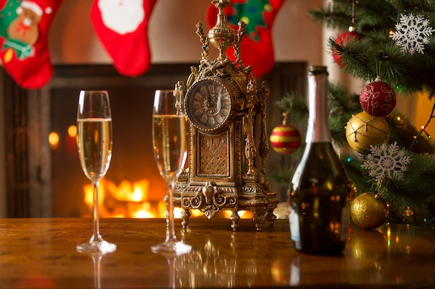 Close-up van twee glazen champagne op tafel naast de oude klok die middernacht toont in de woonkamer die is ingericht voor kerstmis. concept van wachten op nieuwjaar