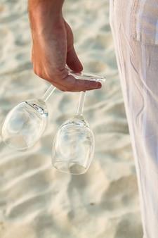 Close-up van twee glazen in hand bij de mens die blootvoets op het strand loopt