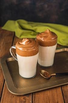Close up van twee glazen met trendy koffie dalgona gemaakt door instant koffie met water en suiker te kloppen