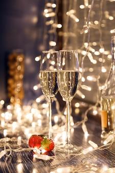 Close-up van twee glazen witte wijn in transparante kristallen glazen en lichte slingers