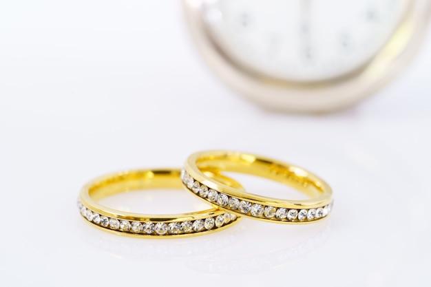 Close-up van twee gouden trouwringen op witte achtergrond