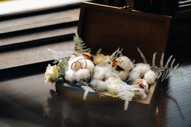 Close-up van twee gouden trouwringen voor een bruiloft in een decoratieve doos met bloemen