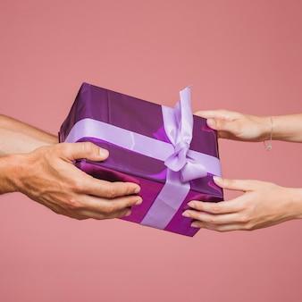 Close-up van twee handen met paarse geschenkdozen tegen gekleurde achtergrond