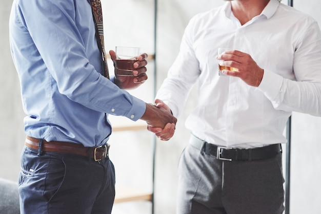 Close-up van twee internationale zakenmensen hebben een goede deal en houden whiskyglazen vast
