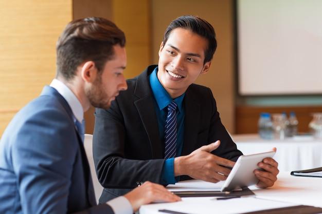 Close-up van twee lachende medewerkers met tablet
