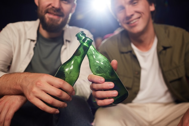 Close-up van twee mannelijke vrienden glimlachend en rammelende bierflesjes tijdens het kijken naar film in bioscoop, kopie ruimte