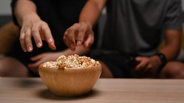 Close-up van twee mannen die op de bank zitten en popcorn eten.