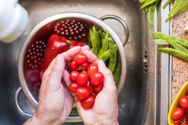 Close up van twee menselijke handen met rode kleine tomaten. achtergrond van rode en groene groenten