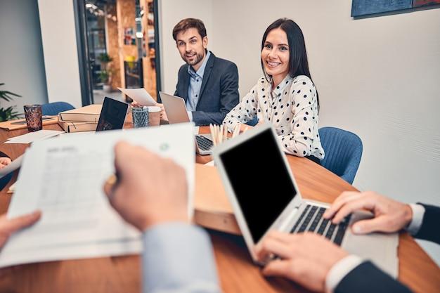 Close-up van twee mensen, vrouw en man die aan het bureau zitten terwijl ze een werkvraag op kantoor bespreken