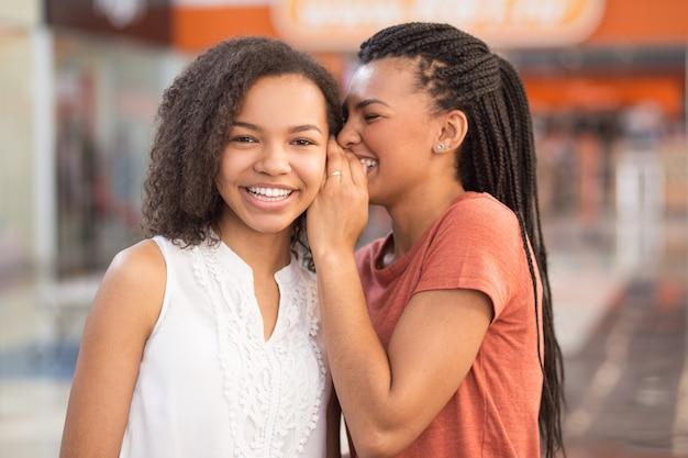 Close-up van twee mooie zwarte meisjes delen geheimen
