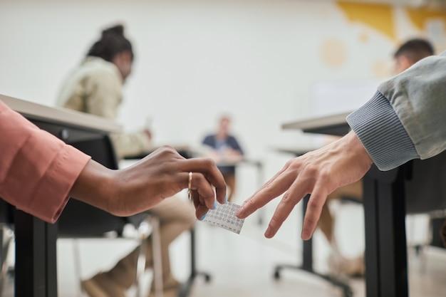 Close-up van twee onherkenbare studenten die een spiekbriefje doorgeven tijdens het examen op school, kopieer ruimte