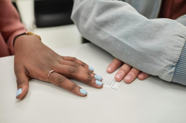 Close-up van twee onherkenbare studenten die een spiekbriefje passeren en wit stiekem examen doen op school, kopieer ruimte