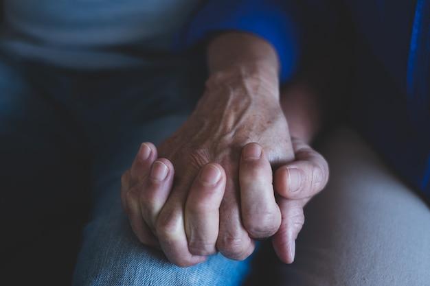 Close-up van twee oude handen van een paar senioren die samen hun handen thuis vasthouden - wees voorzichtig en verliefd op levensstijl