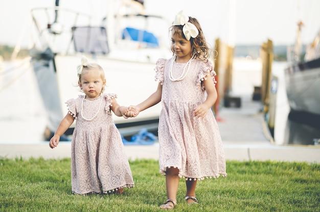 Close-up van twee schattige babymeisjes in soortgelijke jurken wandelen in de buurt van de haven