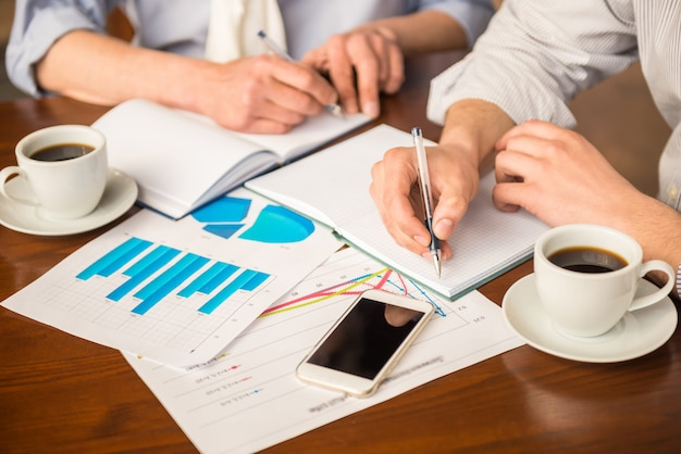 Close-up van twee succesvolle zakenlieden met papieren.