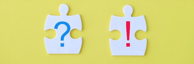 Close-up van twee verschillende stukken voor witte puzzel op gele achtergrond