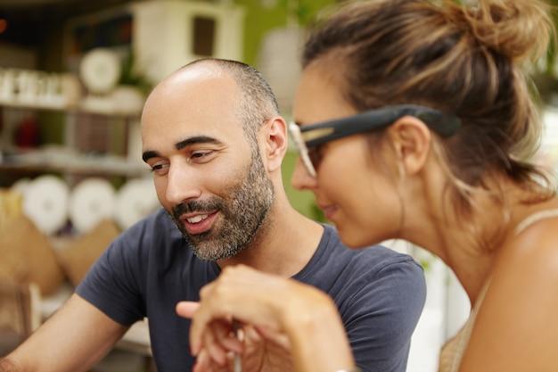 Close-up van twee vrienden die samen vrije tijd doorbrengen, iets online kijken op een elektronische gadget, surfen op internet, genieten van gratis wi-fi, zittend in het restaurant op de stoep tijdens de lunch
