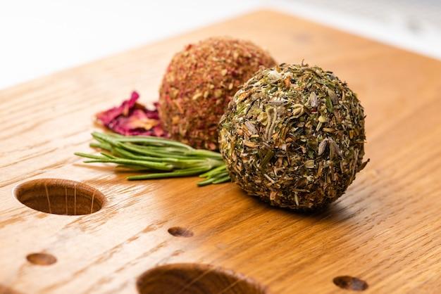 Close-up van twee zachte kaasballen labne met kruiden op houten bord