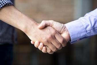 Close-up van twee zaken mannen schudden handen