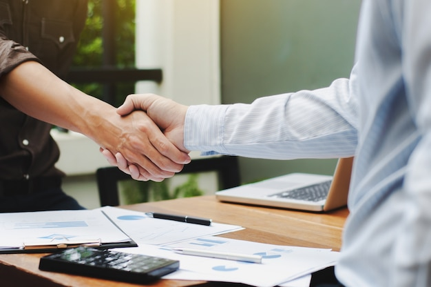 Close-up van twee zakenlieden handen schudden met data-documenten op de tafel