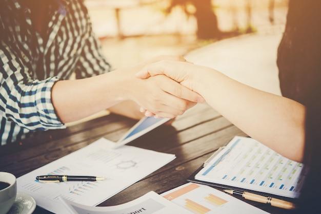 Close-up van twee zakenlieden handen schudden terwijl ze op de werkplek zitten.