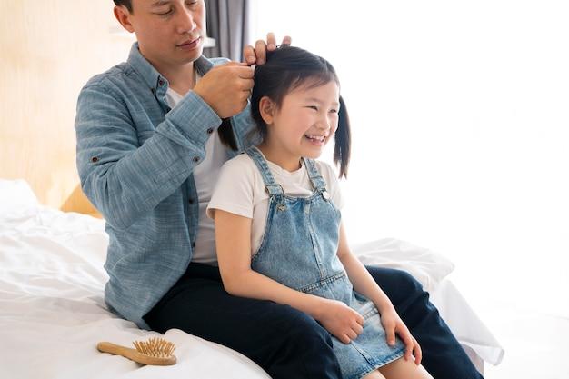 Close-up van vader die het haar van een meisje vastbindt
