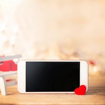 Close-up van valentijnsdag achtergrond ontwerpsjabloon concept met smartphone