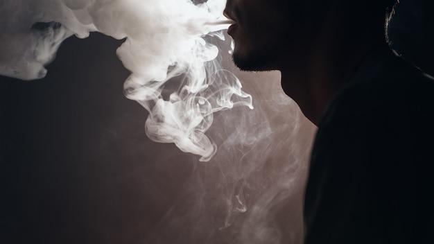 Close - up van vaper man ademt een wolk van stoom uit. elektronische sigaret mod