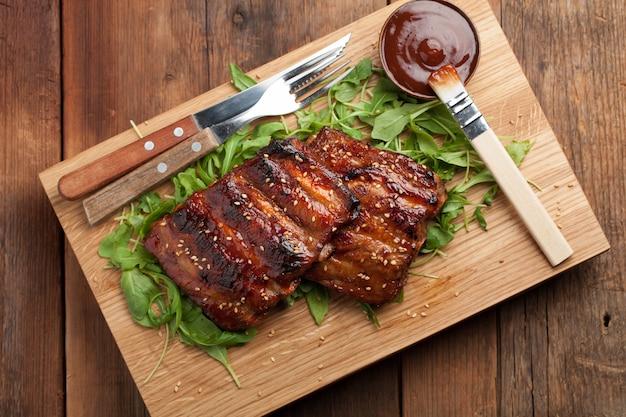Close-up van varkensvleesribben met bbq saus worden geroosterd die.