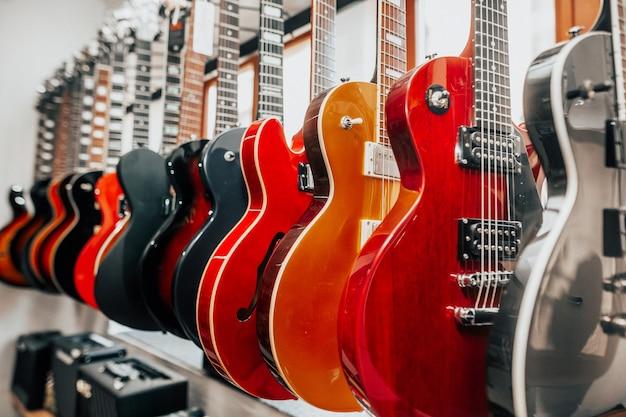 Close-up van veel elektrische gitaren in een rij in de instrumentale winkel, muziekinstrument concept