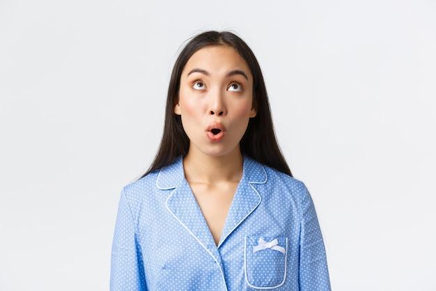 Close-up van verbaasd en onder de indruk kawaii aziatisch meisje in blauwe pyjama reageert op geweldig nieuws, kijkt verwonderd op en zegt wow, staand verbaasd over witte achtergrond.