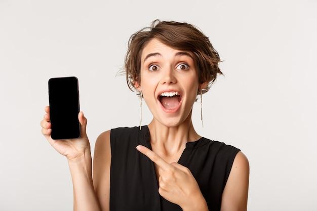 Close-up van verbaasd gelukkig meisje wijzende vinger op smartphonescherm, staande over wit.