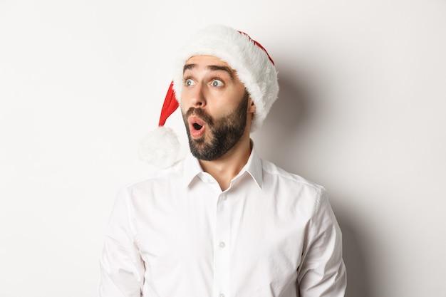 Close-up van verbaasde bebaarde man in kerstmuts, kijkend naar links met verbaasd gezicht, kerst promo-aanbieding, staande op witte achtergrond.