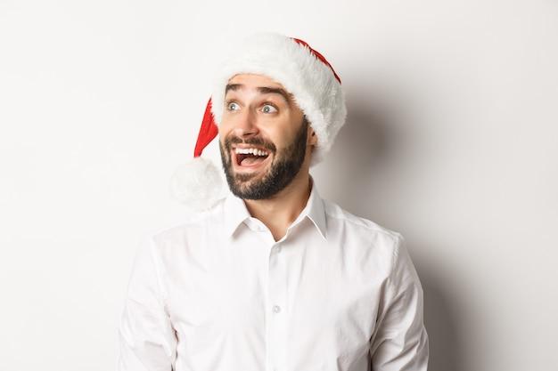 Close-up van verbaasde bebaarde man in kerstmuts, op zoek naar links met opwinding, kerst promo aanbieding, staande op witte achtergrond.