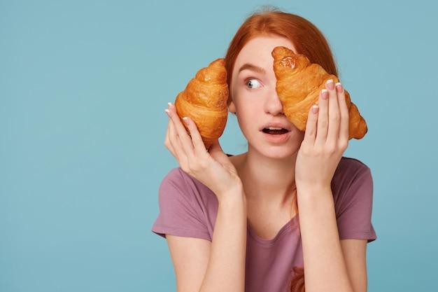 Close-up van verbaasde en verbaasde roodharige vrouw geïsoleerd op een blauwe muur met twee croissants in haar handen