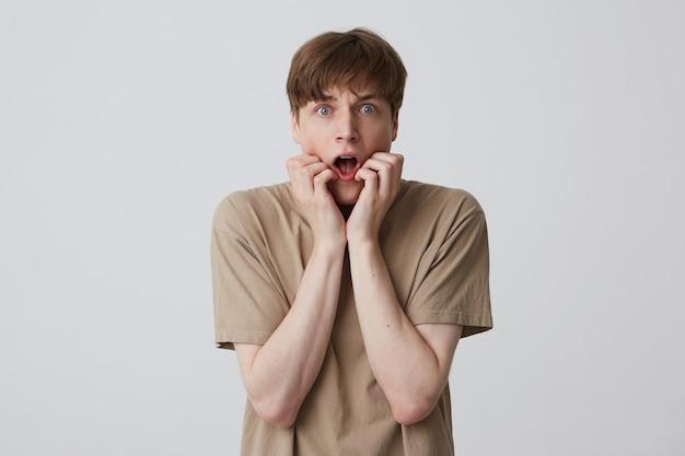 Close-up van verbijsterd bang jonge man met geopende mond draagt beige t-shirt staan en schreeuwen