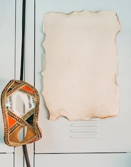 Close-up van verbrande lege pagina met partij oogmasker op kastdeur