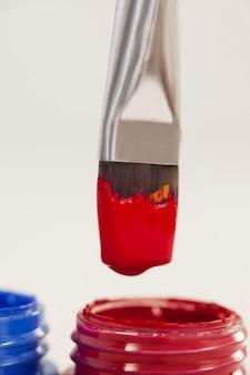Close-up van verfborstel ondergedompeld in rode kleur tegen wit oppervlak