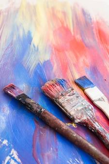 Close-up van verfborstels en abstracte geweven achtergrond