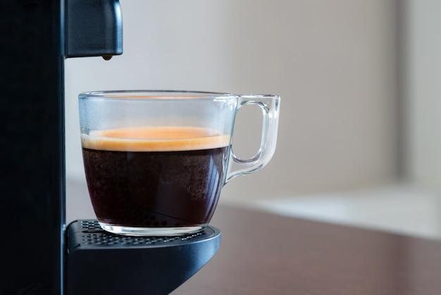 Close-up van verfrissende espresso gieten van capsulemachine in een kopje thuis.