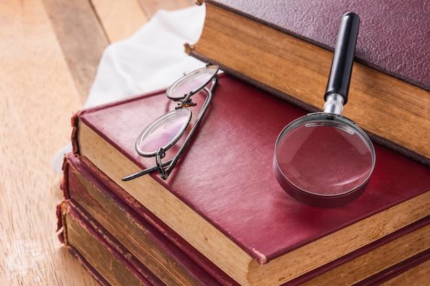 Close-up van vergrootglas op stapel oude boeken